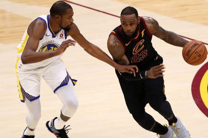 Pebasket megabintang Cleveland Cavaliers, LeBron James (jersey hitam), berupaya melewati penjagaan pemain Golden State Warriors, Kevin Durant, pada laga gim ketiga seri final NBA 2018 di Quicken Loans Arena, Cleveland, Ohio, Amerika Serikat, Kamis (7/6/2018).