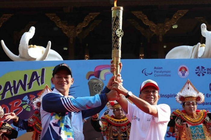 Ketua Umum Inapgoc Raja Sapta Oktohari (kiri) memegang obor yang digunakan pada pawai obor jelang Asian Para Games 2018 di Bali, Minggu (16/9/2018).