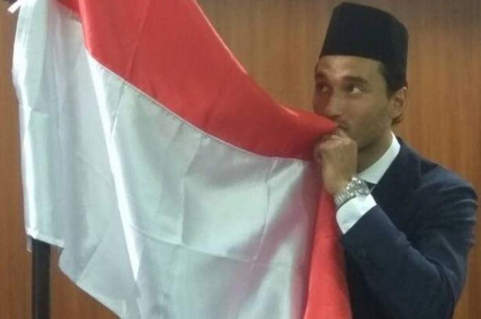 Pose pemain naturalisasi Indonesia, Ezra Walian, saat mencium bendera merah putih selepas disumpah menjadi WNI di Kanwil Kemkumham, Cawang, Jakarta Timur, Kamis (18/5/2017).
