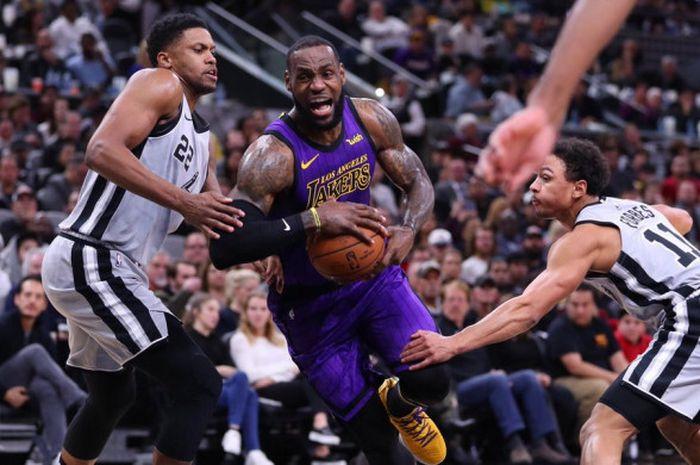 Pemain LA Lakers, LeBron James (jersey ungu), saat berusaha menembus pertahanan San Antonio Spurs da