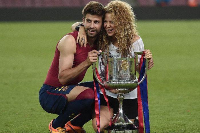 Pemain FC Barcelona dengan istrinya, Shakira, berpose bersama trofi Piala Raja Spanyol seusai laga