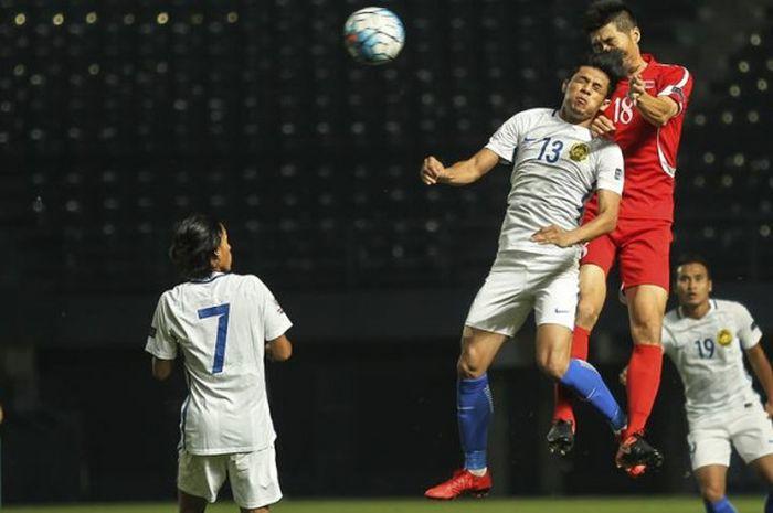 Duel udara antara penyerang timnas Malaysia, Syafiq Ahmad (13) dengan gelandang timnas Korut,Ri Yong-Chol pada laga Kualifikasi Piala Asia 2019 di Stadion New I-Mobile, Buriram, Thailand, 14 November 2017.