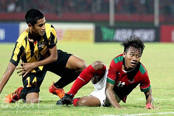 Gelandang Timnas U-16 Indonesia Mohammad Supriadi (kanan), dilanggar pemain Malaysia pada laga semifinal Piala AFF U-16 2018 di Stadion Gelora Delta Sidoarjo, Jawa Timur, Kamis (09/08/2018) malam.