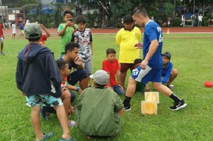Kim Jeffrey Kurniawan berlatih didampingi fisioterapi Benidektus Adi Priyanto, dikerumuni anak-anak dan menjadi bahan tontonan.