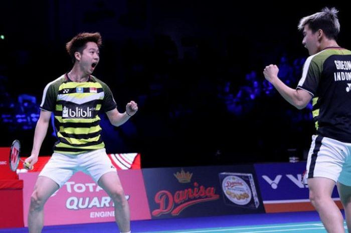 Pasangan ganda putra Indonesia, Marcus Fernaldi Gideon/Kevin Sanjaya Sukamuljo, bereaksi setelah memastikan gelar Denmark Open 2018 di Odense Sports Park, Minggu (21/10/2018).