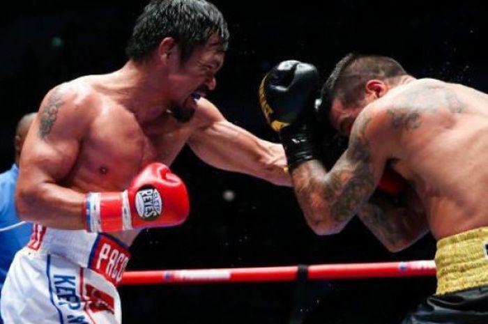 Manny Pacquiao (kiri) saat melesatkan pukulan ke Lucas Matthysse (kanan) pada duel yang digelar di Axiata Arena,  Kuala Lumpur, Malaysia, Minggu (15/7/2018).