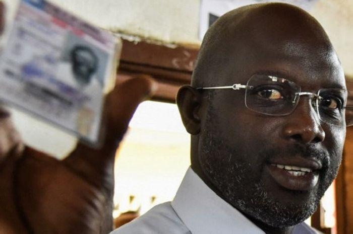 Mantan pemain internasional Liberia yang pernah membela AC milan, George Weah memperlihatkan kartu p