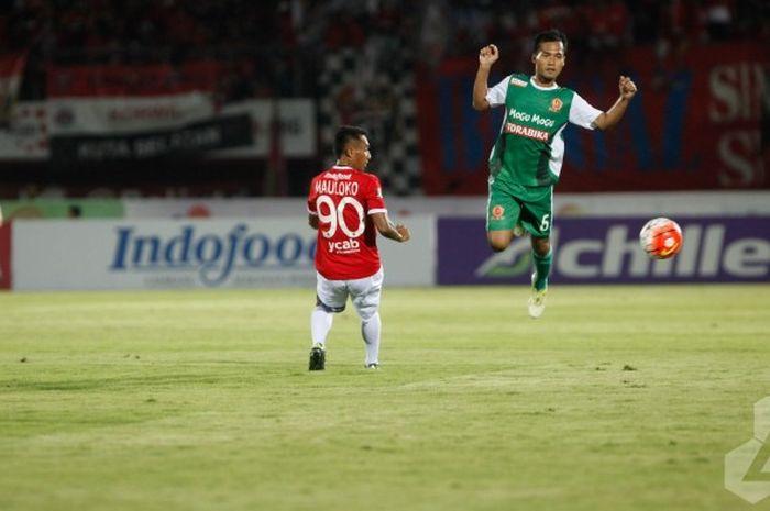 Bek kiri PS TNI, Syaiful Ramadhan (kanan) melompat menghindari pemain Bali United, Yulius Mauloko pa