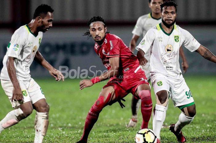 Gelandang Persija Jakarta, Rohit Chand, dikawal dua pemain Persebaya, Izaac Wanggai (kiri) dan Nelson Alom (kanan), di Stadion PTIK, Jakarta, Selasa (26/6/2018).