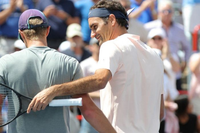 Roger Federer (kiri) menyapa lawannya