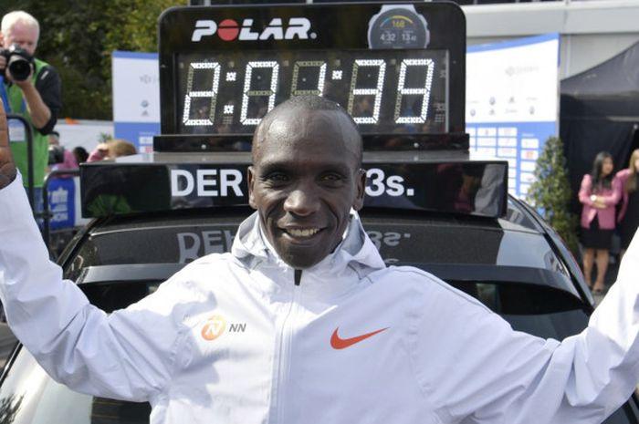 Pelari asal Kenya, Eliud Kipchoge, merayakan catatan waktu rekor dunia yang ia torehkan di Berlin Marathon, Minggu (16/9/2018).