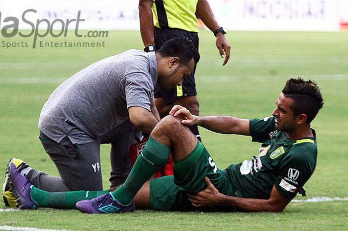 Otavio Dutra menerima perawatan dari tim medis Persebaya saat mengalami cedera.