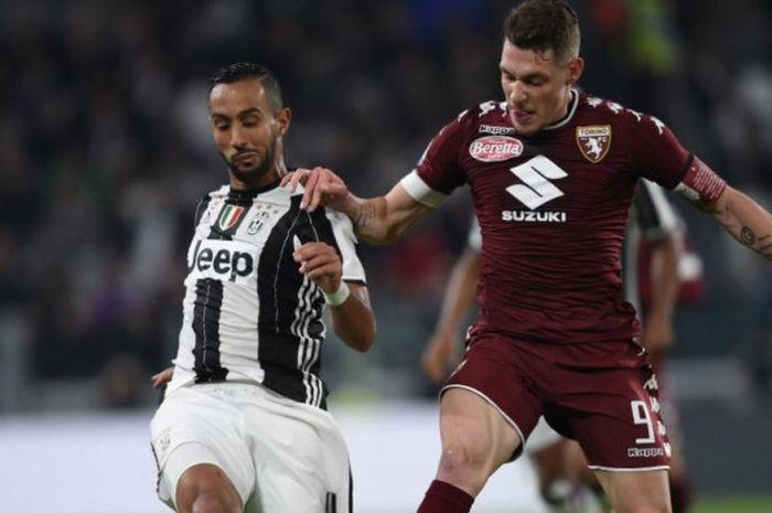Striker Torino, Andrea Belotti (kanan), berduel dengan bek Juventus, Medhi Benatia, dalam partai Lig