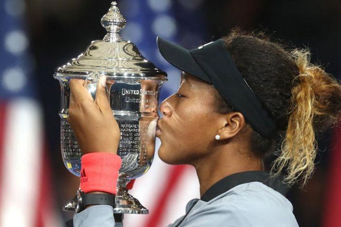 Petenis Jepang, Naomi Osaka, mencium trofi Grand Slam pertamanya usai menang 6-2, 6-4 atas Serena Wi
