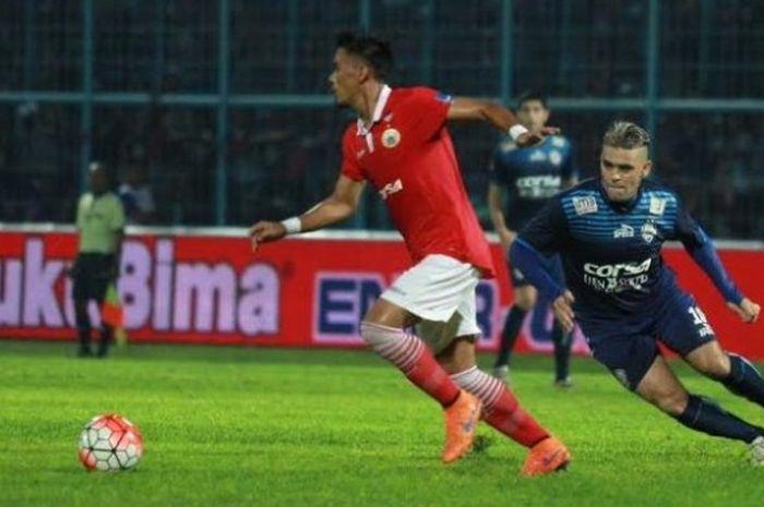 Striker Arema, Cristian Gonzales mencoba merebut bola dari penguasaan bek Persija, Maman Abdurahman