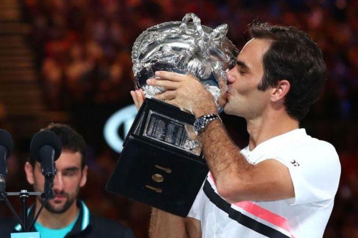 Petenis tunggal putra Swiss, Roger Federer, mencium trofi yang dia raih seusai menjuarai turnamen Gr