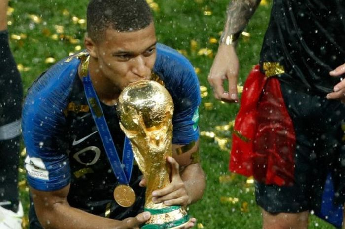 Penyerang Prancis, Kylian Mbappe, mencium trofi juara Piala Dunia 2018 setelah timnya menekuk Kroasia 4-2 pada laga final di Stadion Luzhniki, Moskow, 15 Juli 2018.