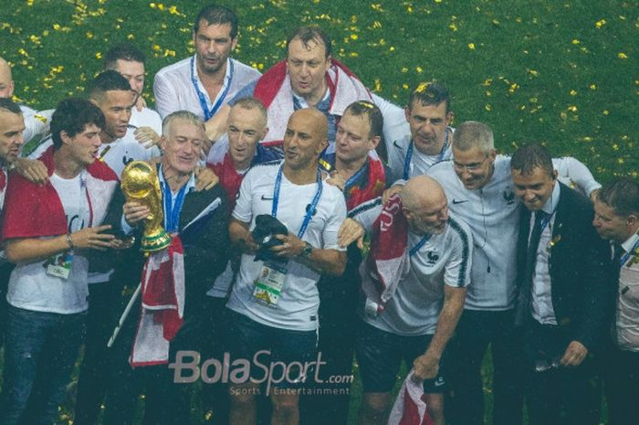 Pelatih Prancis, Didier Deschamps, memegang  trofi juara Piala Dunia 2018 didampingi stafnya.