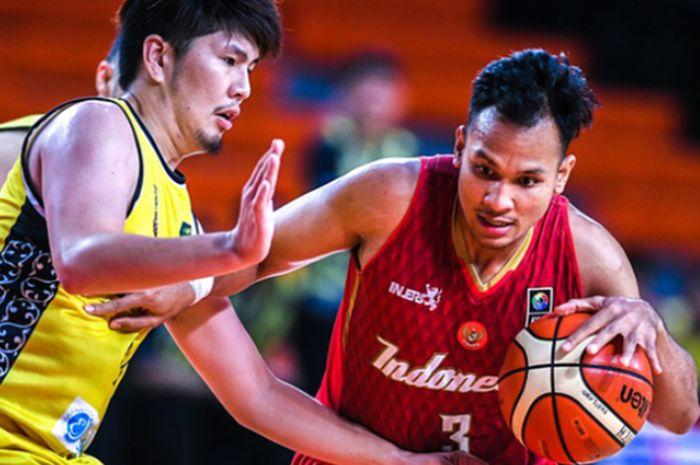 Pemain timnas basket Indonesia, Kaleb Ramot Gemilang, melewati hadangan pemain Brunei Darussalam pad