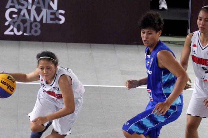 Pemain tim basket 3x3 putri Indonesia, Agustin Elya Gradita Retong (kiri), melewati pemain Thailand pada laga babak penyisihan grup test event Asian Games 2018, di Center Court, GBK, Senayan, Jumat (1/12/2017).
