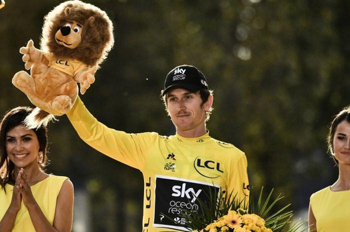 Pebalap sepeda Britania Raya, Geraint Thomas, melakukan selebrasi di atas podium setelah memastikan menjuarai Tour de France 2018, Sabtu (29/7/2018).