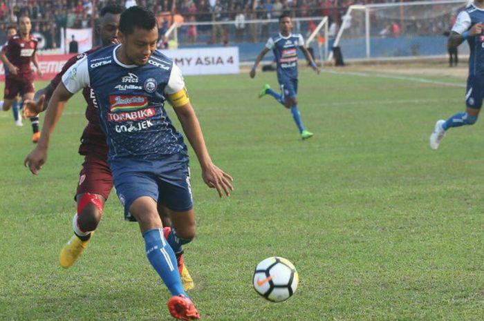 Aksi kapten Arema FC, Hamka Hamzah (depan) saat mengamankan bola dari penyerang PSM Makassar, Guy Ju