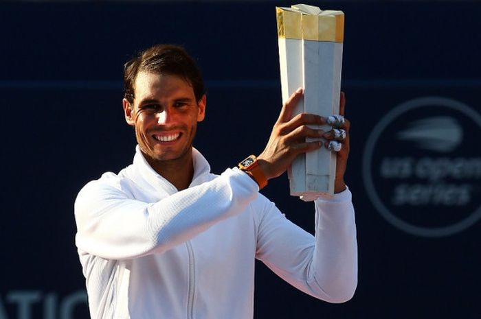 Petenis tunggal putra Spanyol, Rafael Nadal, mengangkat trofi yang diraih setelah menjuarai turnamen Rogers Cup 2018 di Toronto, Kanada, Minggu (12/8/2018).