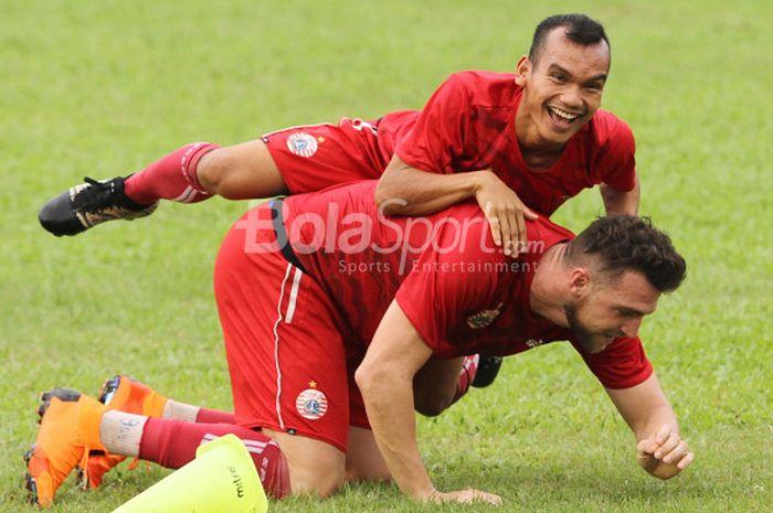 Riko Simanjuntak bercanda dengan Marko Simic pada sela sesi latihan Persija Jakarta di Lapangan