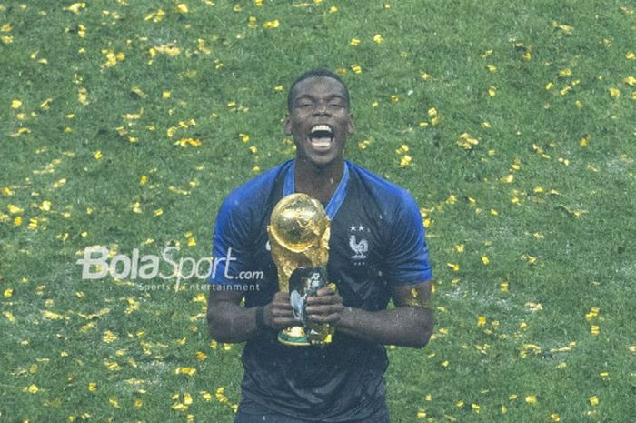 Gelandang asal Prancis, Paul Pogba, memegang trofi Piala Dunia usai mengalahkan Kroasia dalam la