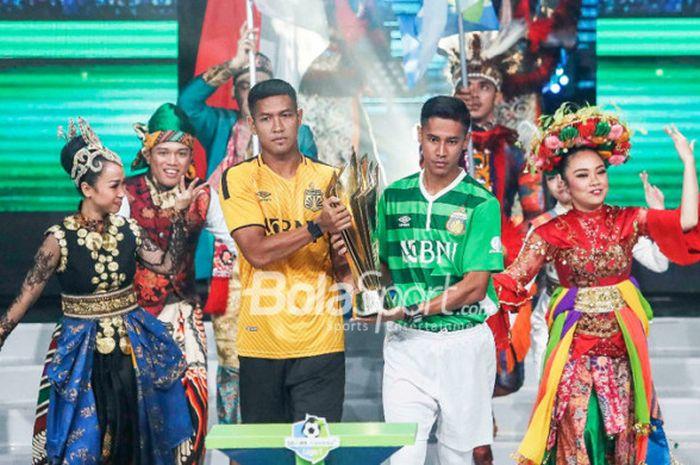 Pemain Bhayangkara FC,  Jajang Mulyana dan Indra Kahfi, membawa trofi Liga 1 di acara peluncuran kompetisi pada Senin (19/3/2018).
