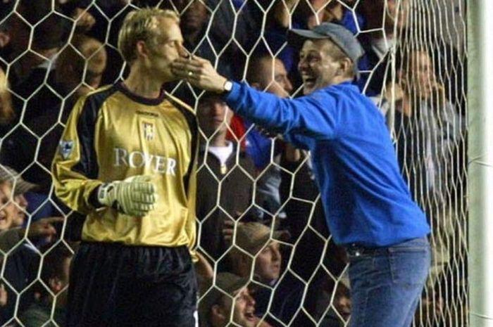 Suporter Birmingham City, Michael Harper (kanan), masuk ke dalam lapangan pertandingan untuk mengejek kiper Aston Villa, Peter Enckelman, yang melakukan blunder di laga Liga Inggris yang berlangsung di Stadion St Andrew's, Birmingham, Inggris, pada 16 September 2002.