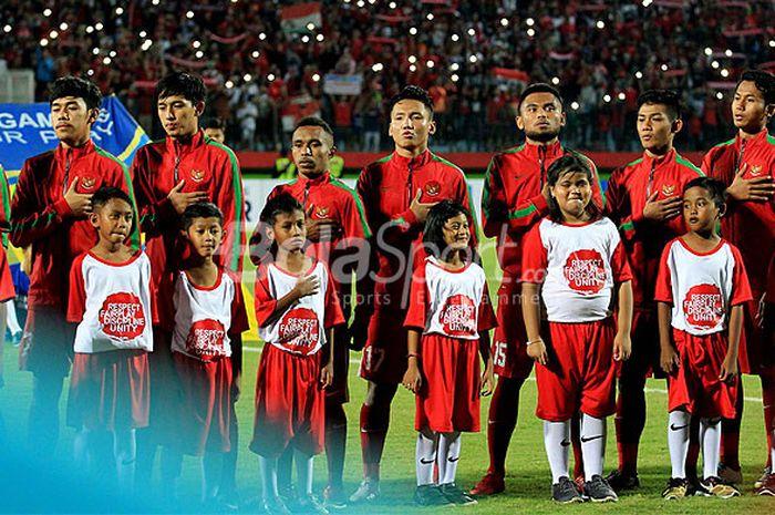 Pemain timnas U-19 Indonesia menyanyikan lagu kebangsaan Indonesia menjelang dimulainya laga Grup A Piala AFF U-19 2018 antara Indonesia melawan Laos di Stadion Gelora Delta Sidoarjo, Jawa Timur, Minggu (01/07/2018) malam.