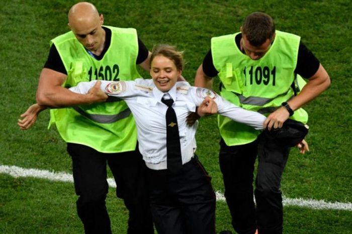 Petugas mengamankan penyusup yang masuk ke lapangan dalam laga final Piala Dunia 2018 Prancis vs Kroasia di Stadion Luzhniki, Moskow, 15 Juli 2018.