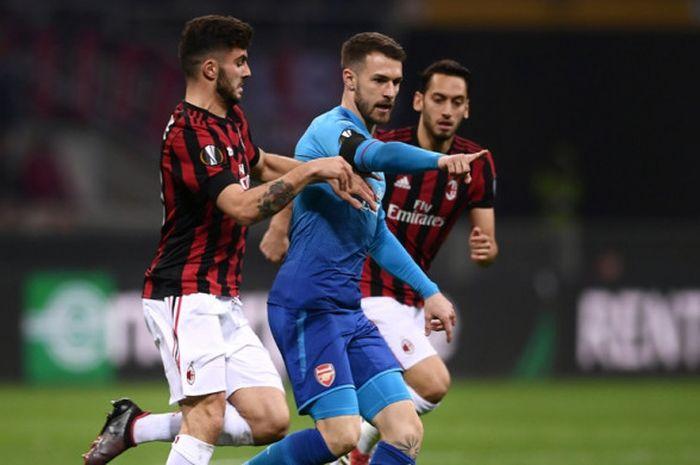 Penyerang AC Milan, Patrick Cutrone (kiri), berduel dengan gelandang Arsenal, Aaron Ramsey, dalam laga leg pertama babak 16 besar Liga Europa di Stadion San Siro, Milan, Italia, pada 8 Maret 2018.