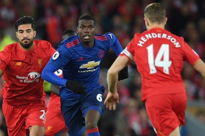 Gelandang Manchester United, Paul Pogba, (tengah) berduel melawan pemain Liverpool, Jordan Henderson dan Emre Can (kiri), di Stadion Anfield (17/10/2016).