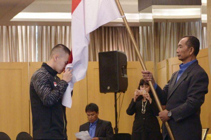 Marcus Fernaldi Gideon sedang mencium bendera Indonesia pada acara pelepasan tim Piala Thomas dan Uber di Hotel Atlet Century, Jakarta, Selasa (8/5/2018).