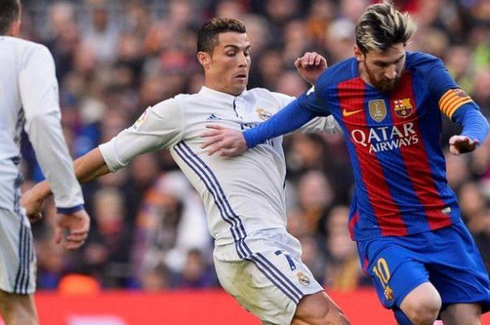 Lionel Messi (kanan) dan Cristiano Ronaldo berebut bola dalam partai Liga Spanyol antara FC Barcelona dan Real Madrid di Stadion Camp Nou, Barcelona, 3 Desember 2016.