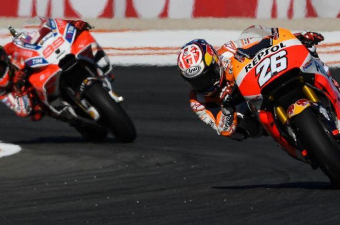 Untuk mengatasi kurangnya beban terhadap motor, Dani Pedrosa (kanan) segera mengangkat motornya sambil tetap menggantungkan tubuhnya di samping saat berakselerasi melewati tikungan.