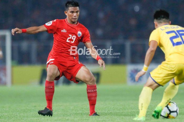 Pemain Persija, Sandi Darma Sute, mencoba menghentikan pemain Song Lam Nghe An di laga Grup H Piala