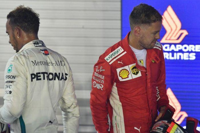 Lewis Hamilton (kiri) dan Sebastian Vettel (kanan) setelah menyelesaikan balapan GP Singapura di Sirkuit Jalan Raya Marina Bay, Minggu (16/9/2018).