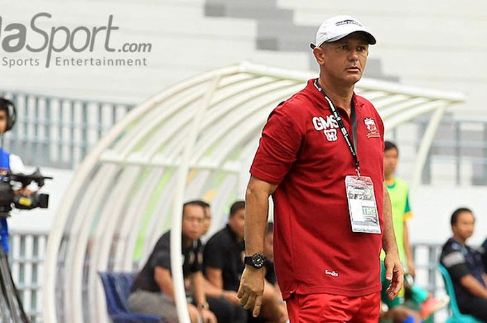 Pelatih Madura United, Gomes de Oliveira, mengamati jalannya laga lanjutan babak penyisihan Piala Gu