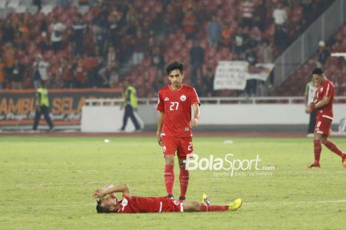 Pemain Persija Jakarta, Fitra Ridwan, mendekati Riko Simanjuntak yang terlentang di lapangan seus