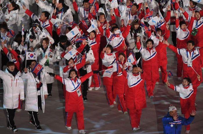 Delegasi Korea Utara dan Korea Selatan melambaikan bendera negara mereka bersama bendera unifikasi Korea pada upacara penutupan Olimpiade Musim Dingin Pyeongchang 2018 di Stadion Pyeongchang, Minggu (25/2/2018).