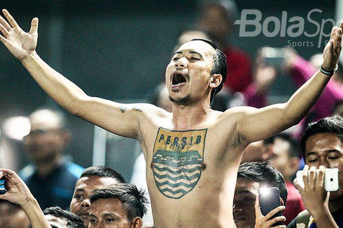 Pendukung Persib Bandung yang dikenal dengan Bobotoh beraksi saat memberi dukungan kepada timnya pada pekan kesepuluh Liga 1 2018 melawan PSM Makassar di Stadion GBLA, Kota Bandung, Rabu (23/05/18).