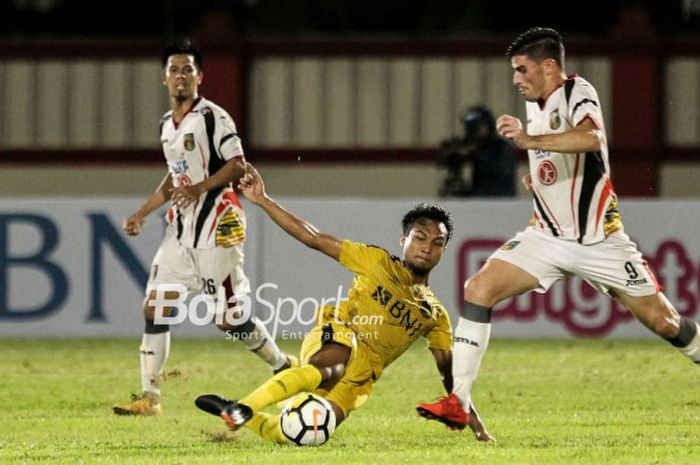 Pemain Bhayangkara FC, Muhammad Hargianto, melepas  tackle ke pemain Mitra Kukar, Fernando Rodriguez