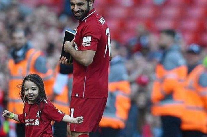 Winger Liverpool, Mohamed Salah, tampak gembira melihat putri kecilnya, Makka, dengan asyiknya bermain bola di lapangan Stadion Anfield sebelum laga melawan Brighton Hove and Albion pada 13 Mei 2018.