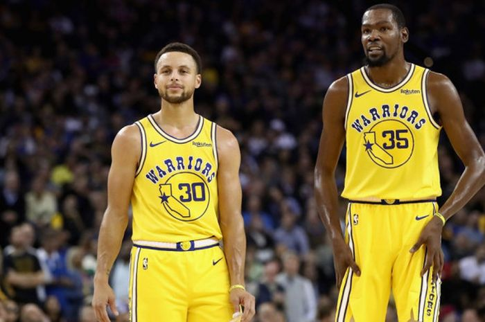 Dua pebasket bintang Golden State Warriors, Stephen Curry (kiri) dan Kevin Durant (kanan), berbincang di sela pertandingan melawan Washington Wizards di Oracle Arena, Oakland, California, AS, Rabu (24/10/2018).