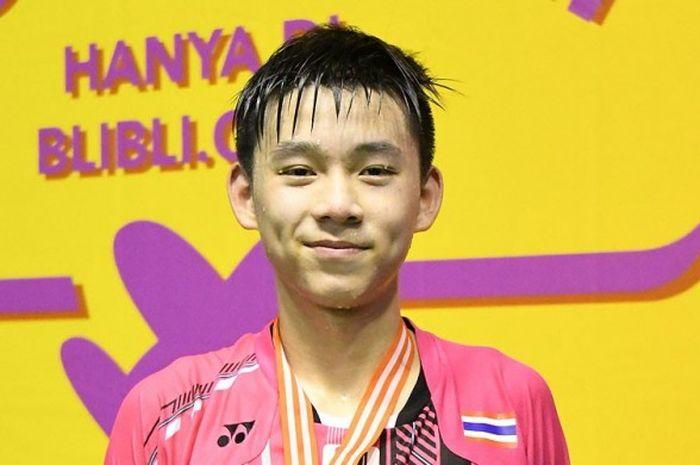 Pebulu tangkis muda asal Thailand, Kunlavut Vitidsarn, berpose usai pengalungan medali juara nomor t