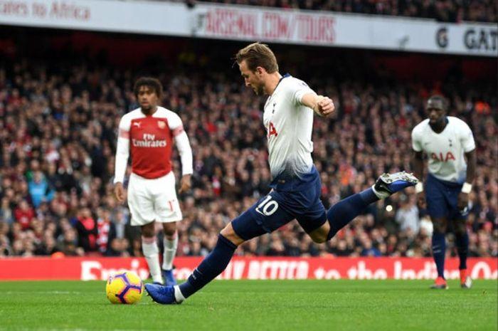Penyerang Tottenham Hotspur, Harry Kane, mengeksekusi penalti pada laga kontra Arsenal di Stadion Emirates, Minggu (2/12/2018).