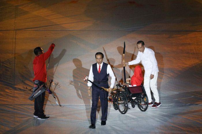 Presiden Joko Widodo berjalan usai memanah batu bertuliskan disability yang berubah menjadi ability